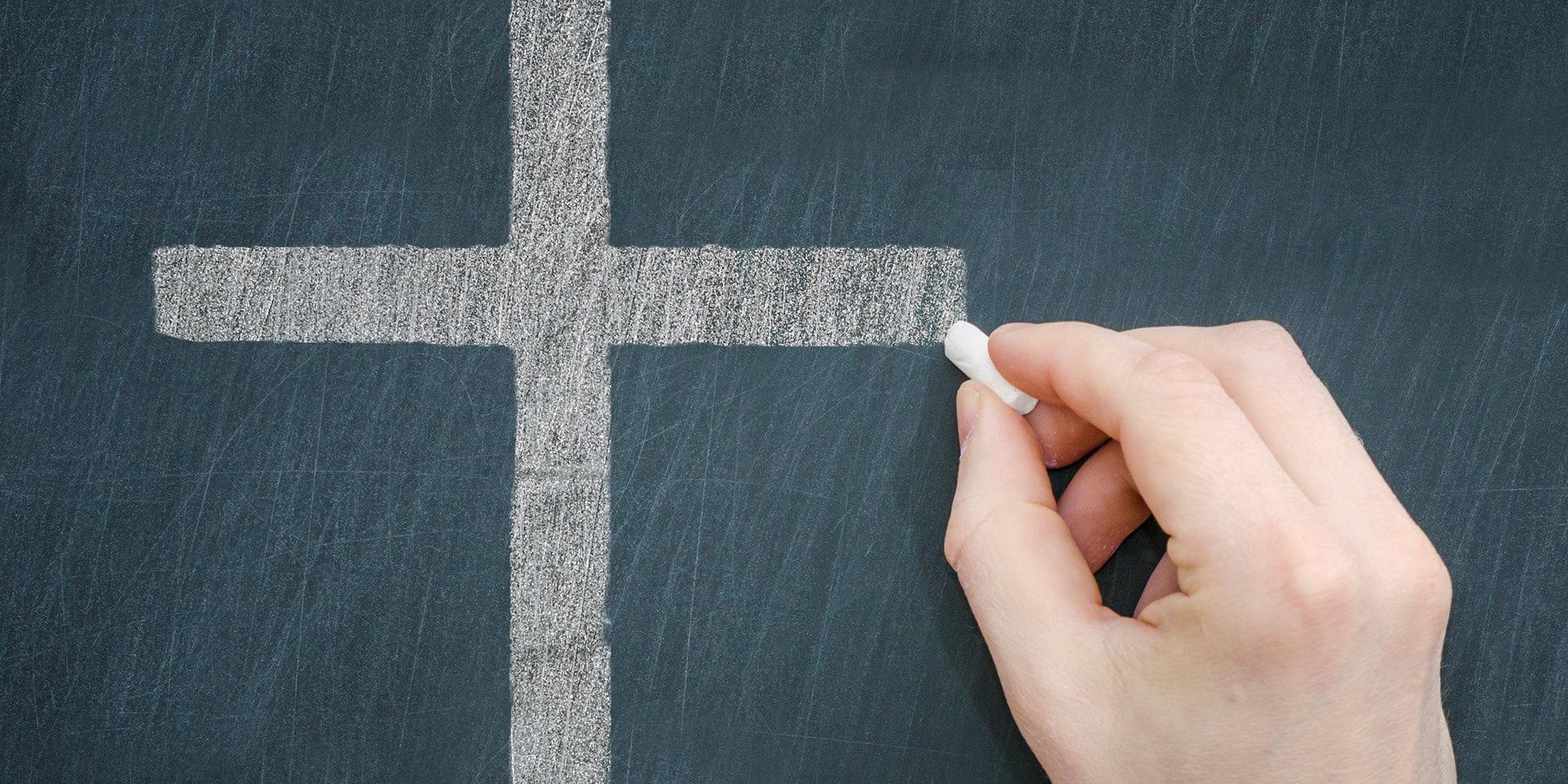 Eine Hand malt mit Kreide ein Kreuz an eine Tafel