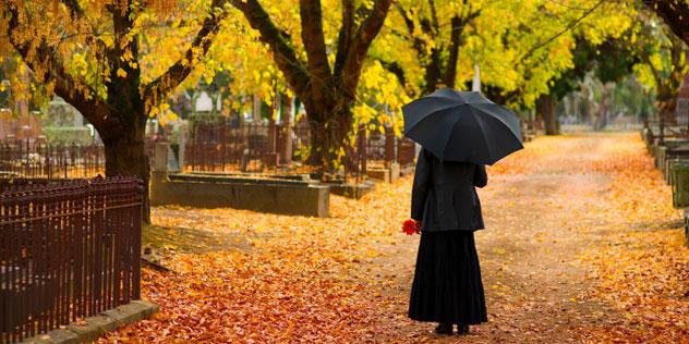 Schwarzgekleidete Frau in einem herbstlichen Park mit bunten Blättern