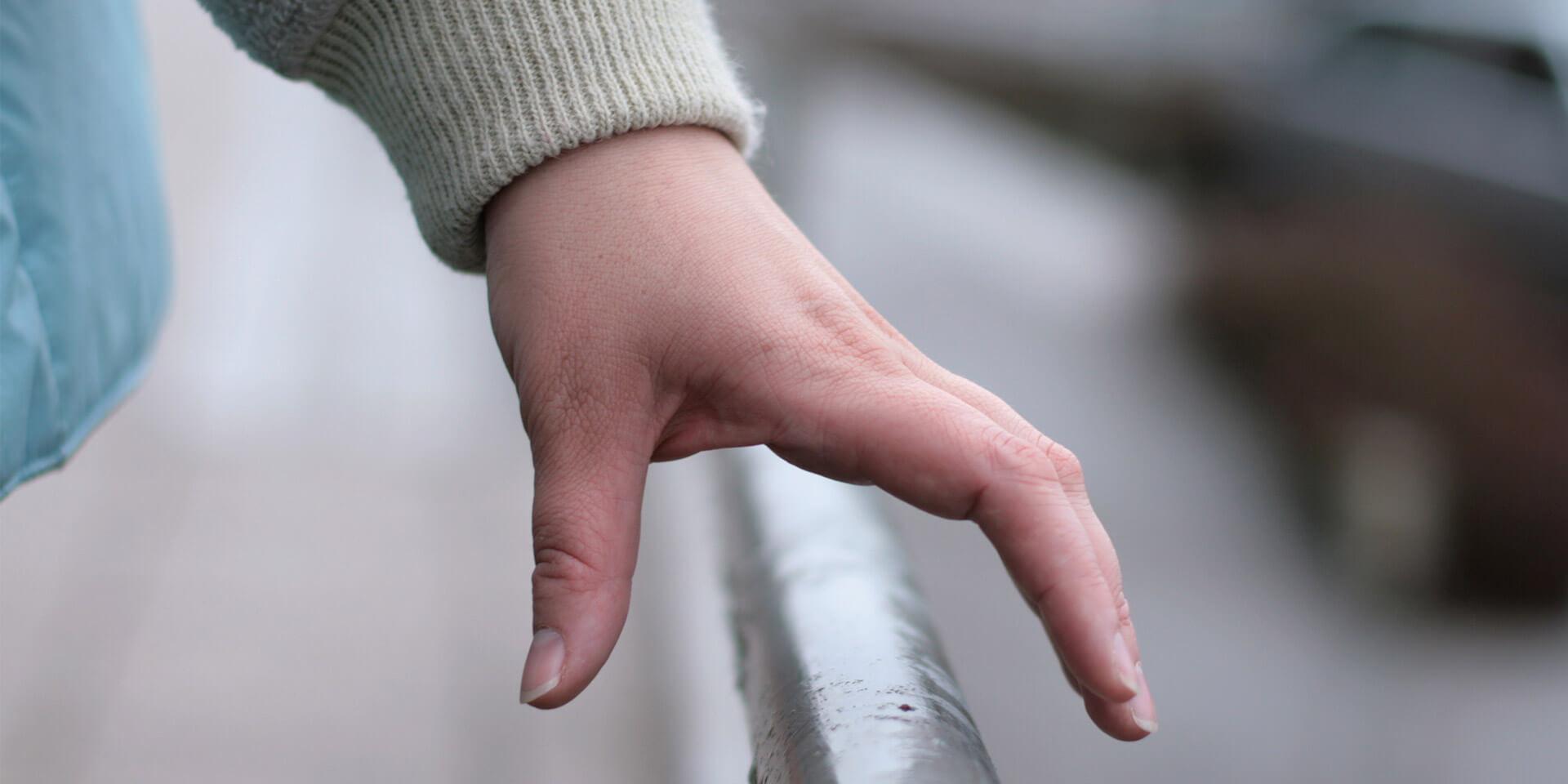 Hand am Geländer