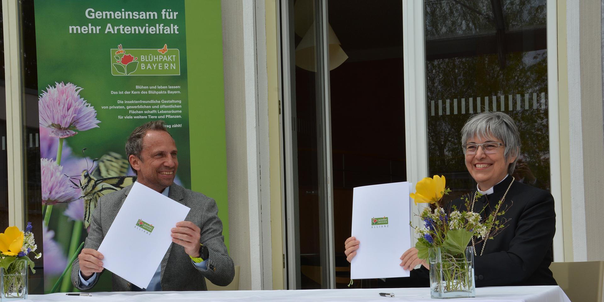 Der bayerische Umweltminister Thorsten Glauber und Regionalbischöfin Dorothea Greiner  bei der Unterzeichnung des Blühpakts