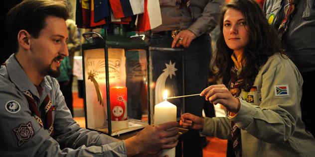 Das Bild zeigt eine Pfadfinderin und einen Pfadfinder mit dem Friedenslicht von Bethlehem