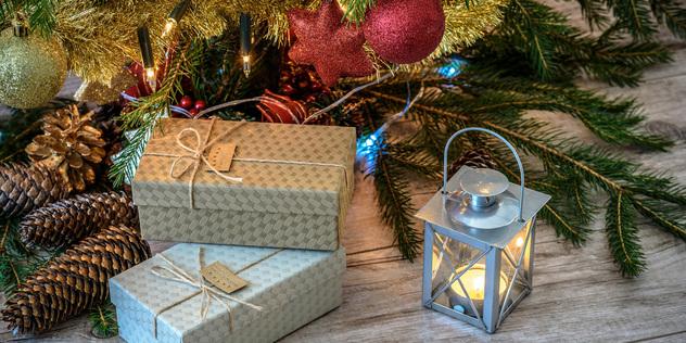 Das Bild zeigt zwei Weihnachtsgeschenke, eine Laterne, ein Tannenzweig mit Kugeln