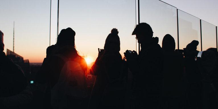 Menschen schauen in den Sonnenuntergang , © Unsplash / Alina Grubnyak