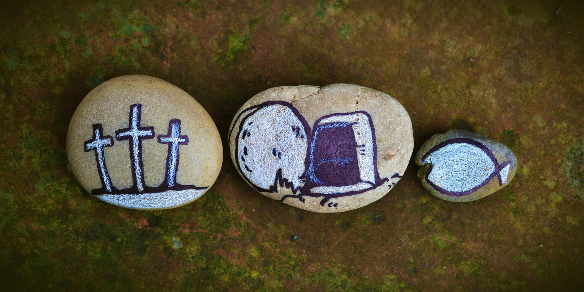 Drei Kreuze, leeres Grab und Fisch auf drei Steine gemalt