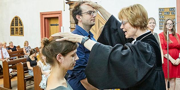 Regionalbischöfin Gisela Bornowski segnet in Würzburg zwei junge Religionslehrkräfte ein.